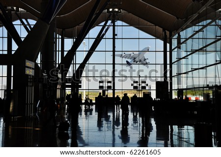 Backlight silhouette of poeple in an airport terminal with an espectacular plane takeoff ouside - stock photo