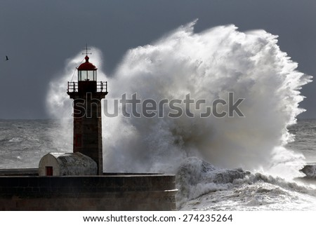 Backlit big stormy wave over lighthouse - stock photo
