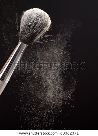 Backlit blowing to red brush with powder making a powder cloud on black background - stock photo