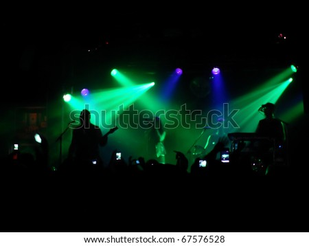 Backlit concert scene with band on stage - stock photo