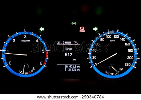 Backlit gauges of an automobile. Blue glowing meters with a white needle. Fuel, tachometer, and speedometer. - stock photo