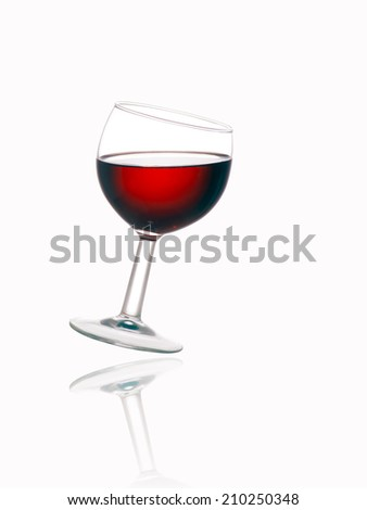 Backlit glass of red wine with reflection over white background. Angled. - stock photo