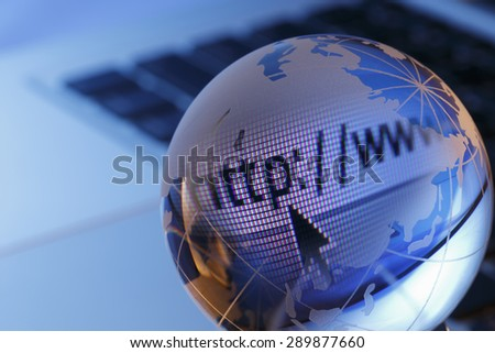 Backlit globe and computer keyboard  with cursor arrow - stock photo
