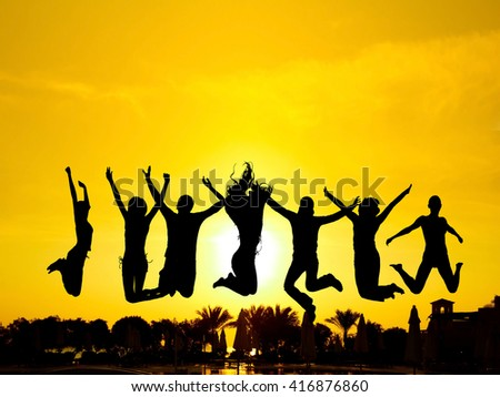 Backlit Group Jumping over Sunset  - stock photo
