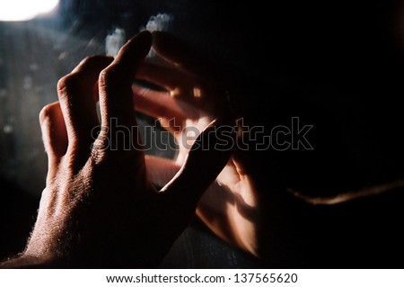 Backlit Hand on Mirror - stock photo
