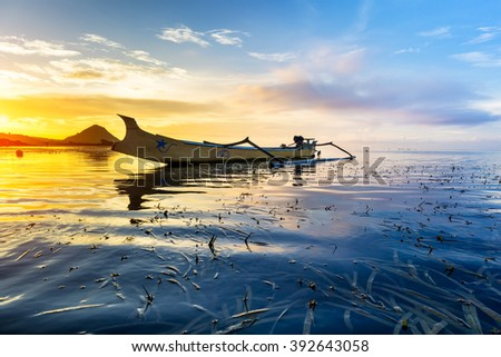 Backlit image of a traditional fishing boat during sunrise at Kuta Beach, Lombok Indonesia.  (Image may contain noise and long exposure motion blur) - stock photo