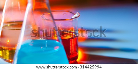 Backlit laboratory test flask containing colorful liquids. Panoramic composition.
