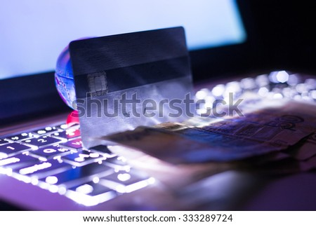 Backlit laptop keyboard with a globe, a credit card and paper money at night. Shallow DOF. - stock photo