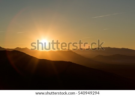 Backlit mountains and plains with a beautiful sunrise