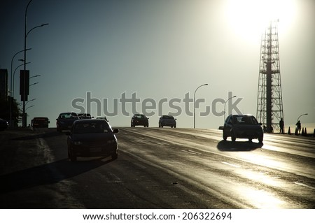 Backlit of a street with cars approaching the camera and a TV tower in the back