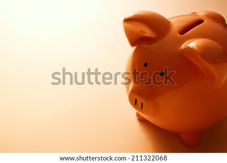 Backlit pink ceramic piggy bank standing facing the camera in a financial, savings and investment concept - stock photo