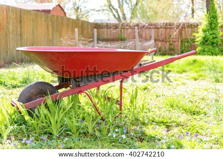 Backlit red wheelbarrow in a backyard in the grass.