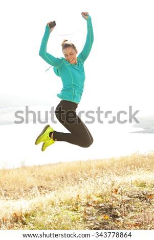 Backlit runner jumping for joy - stock photo