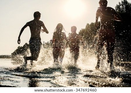 Backlit shot of teenagers running with their feet in the water at the beach during a sunny afternoon during summer break. They are having fun, playing and splashing water around them - stock photo