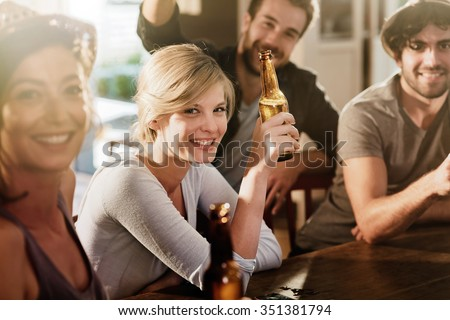 Backlit shot with flare. Friends having a drinks on a sunny evening in a bar, They are sitting with beers. They are wearing casual clothes. Focus on a gorgeous blonde girl touching her bottle. - stock photo