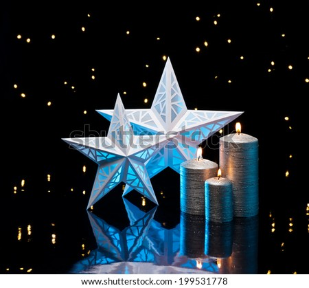Backlit stars in blue with silver candles in front of dark background - stock photo