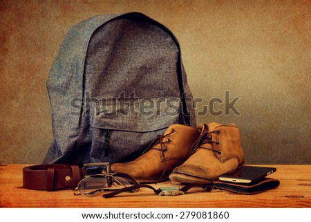 Backpack and boots on wooden table over grunge background