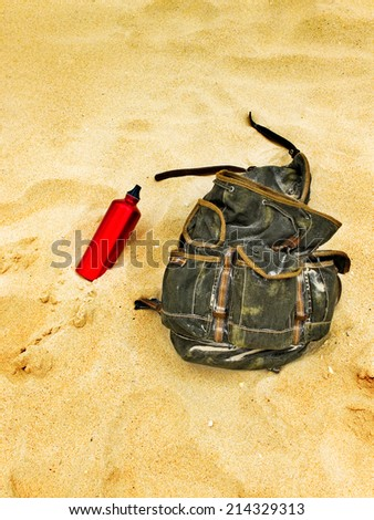 Backpack and canteen water bottle in the sand of a beach. Backpacking traveller taking a break.