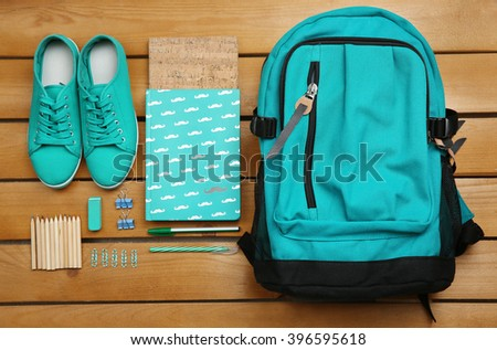 Backpack and school supplies on wooden background, close up. Top view. - stock photo