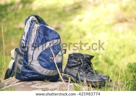 backpack and shoes backpackers in grass - stock photo