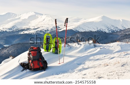 backpack and snowshoe on the background of winter mountains - stock photo