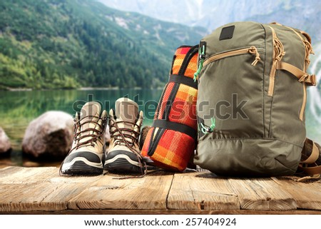 backpack shoes and landscape of green lake in summer time  - stock photo