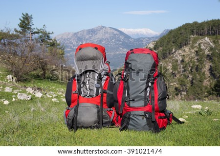 Backpack standing on top of a mountain on the background of snowy mountains. - stock photo