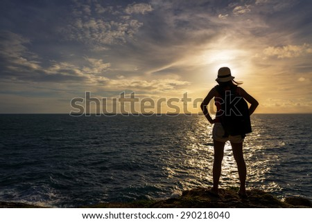 Backpack traveler asia woman standing on sea cliff in sunset, Koh Samet, Rayong, Thailand - stock photo