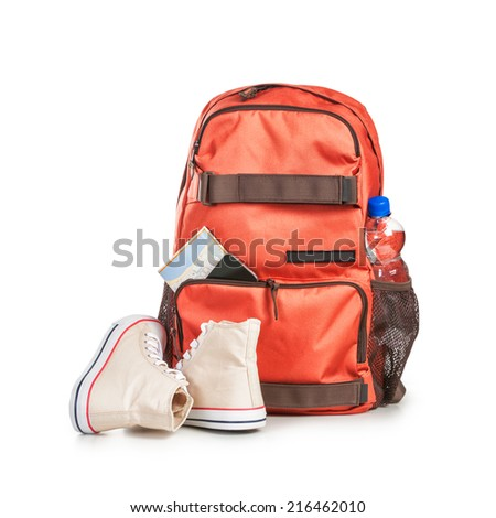 Backpack with bottle of water, smart phone, map and sport shoes isolated on white background. Tourism and travel themes. Clipping path - stock photo