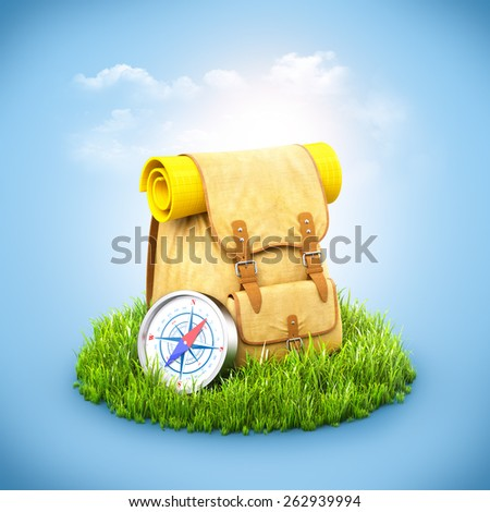 Backpack with  compass  on grass at blue background. Unusual travel background - stock photo