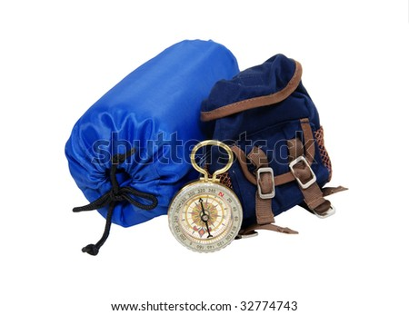 Backpack with rolled up sleeping bag and compass for overnight trips - path included