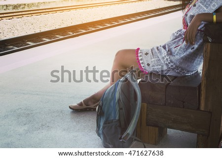Backpack woman at the train station. Travel concept. Vintage tone.