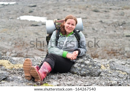 Backpacker a young Caucasian woman sitting on rock in mountains  - stock photo