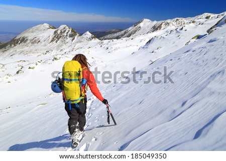 Backpacker carrying climbing gear on the mountain in sunny day