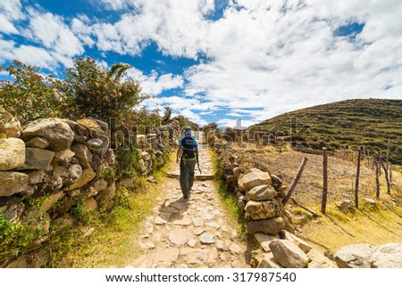 Backpacker exploring the inca's majestic footpaths on Island of the Sun, Titicaca Lake, among the most scenic travel destination in Bolivia. Travel adventures and vacations in the Americas. - stock photo