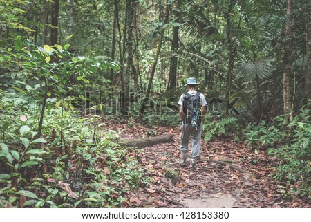 Backpacker exploring the majestic jungle of Kubah National Park, West Sarawak, Borneo, Malaysia. Selective focus, blurred motion, desaturated and toned image, instagram style. - stock photo