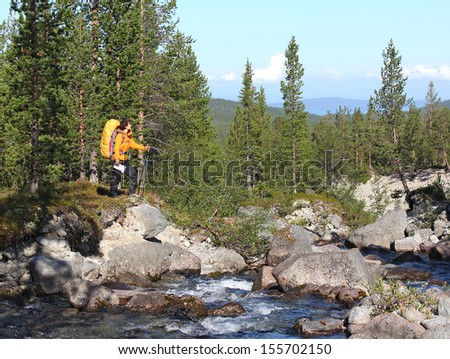 backpacker girl on a rock near the river looking for way, Russia, Hibiny mountain - stock photo