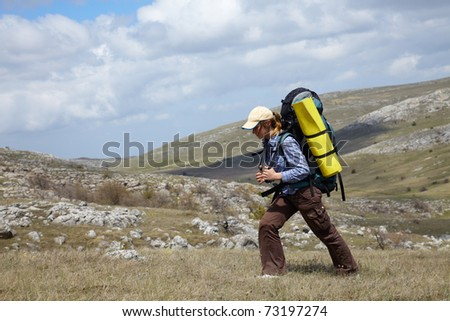 Backpacker girl traveling in spring mountains