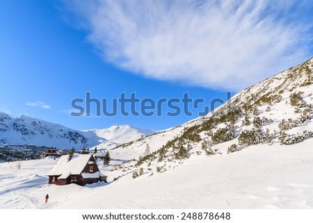 Backpacker in front of wooden mountain hut in winter landscape of Gasienicowa valley, Tatra Mountains, Poland
