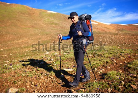 Backpacker in the wilderness mountains - stock photo