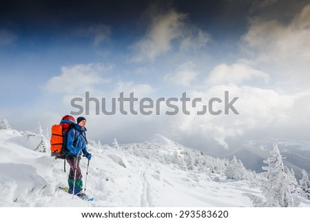 Backpacker in winter mountains - stock photo