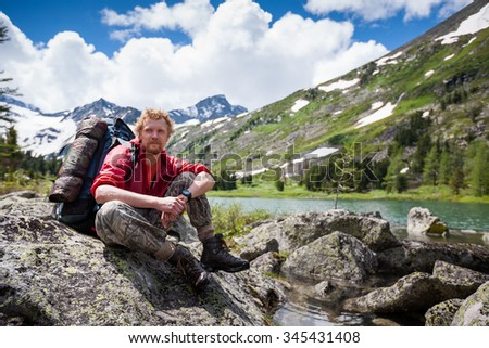 Backpacker is resting while hiking in mountains