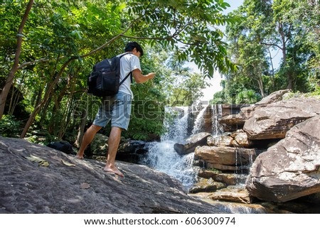 backpacker man use smartphone take photo at waterfall.