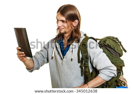 Backpacker man using pc computer tablet browsing surfing the internet. Young hiker backpacking. Modern technology. - stock photo