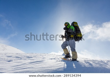 Backpacker man walking in winter mountains on sunny day - stock photo