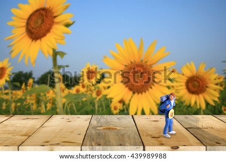 backpacker miniature figure on wood table with nature scene  - stock photo