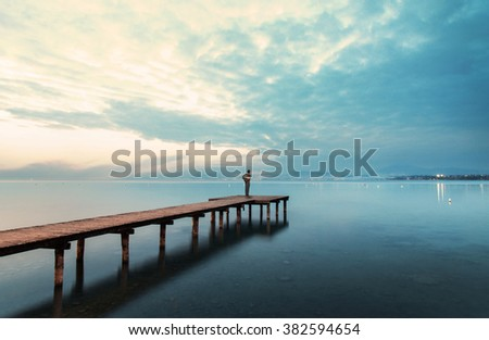 backpacker on a boardwalk looking at the beautiful seascape - stock photo