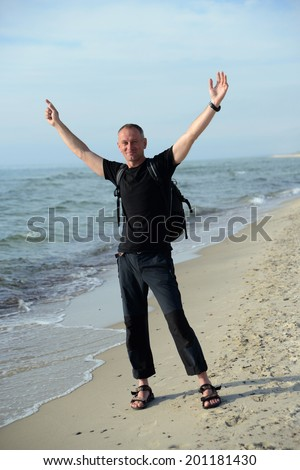 Backpacker on the sandy beach - stock photo