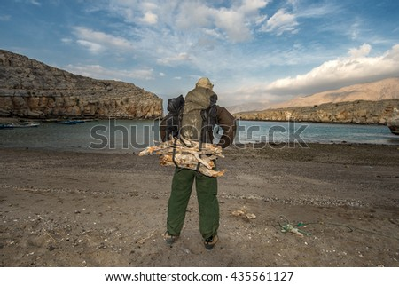Backpacker on the sandy beach, big backpack loaded with firewood