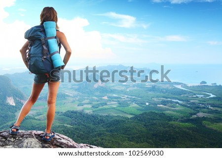 Backpacker on top of a mountain enjoying valley view - stock photo